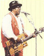 {Bo Diddley playing the Mean Machine guitar}